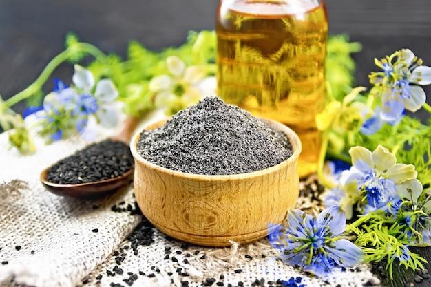 Farinha de cominho preto em uma tigela, sementes em uma colher na serapilheira, óleo na garrafa e galhos nigella sativa com flores azuis e folhas no fundo da placa de madeira