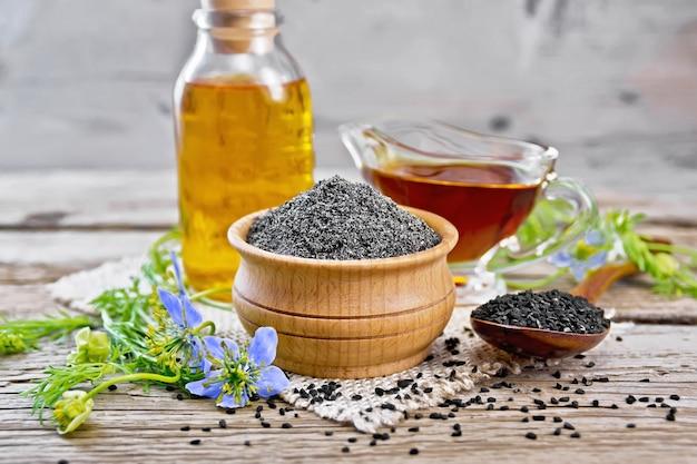 Farinha de cominho preto em uma tigela, sementes em uma colher, óleo em uma garrafa e molheira na serapilheira, raminhos de nigella sativa com flores azuis e folhas na placa de madeira
