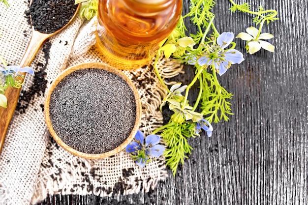 Farinha de kalingi na tigela, sementes na colher, óleo na garrafa, flores azuis no fundo do topo