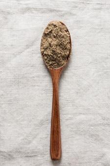 Farinha de linho na colher de pau na toalha de linho. vista do topo. formato vertical.