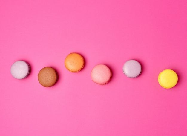 Farinha de macarons macarons cozidos coloridos sobre um fundo rosa
