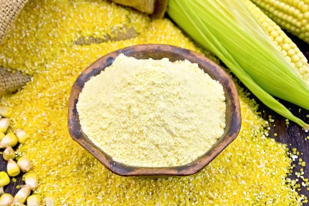 Farinha de milho em uma tigela de barro com grãos, espigas e grãos, um saco em uma placa de madeira escura