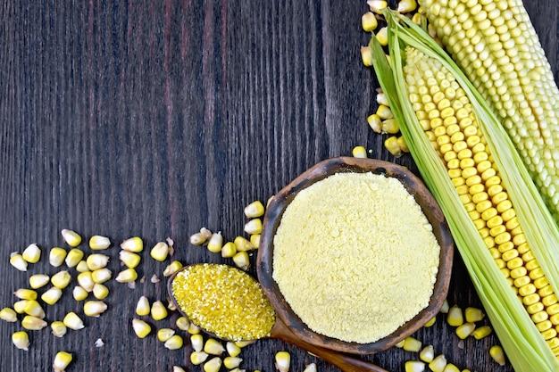 Farinha de milho na tigela e grits na colher, espigas e grãos de milho no fundo de tábuas de madeira