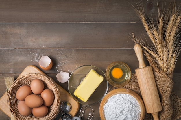 Farinha de pão com ovo fresco, manteiga sem sal e acessórios de panificação em fundo de madeira, prepare-se para o conceito de padaria caseira