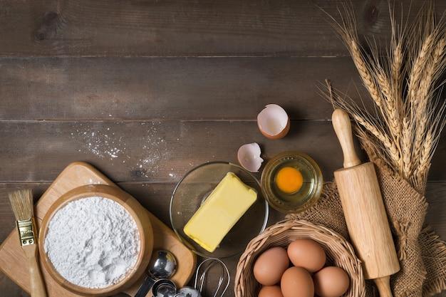 Farinha de pão com ovo fresco, manteiga sem sal e acessórios de panificação na superfície de madeira, preparação para o conceito de padaria caseira