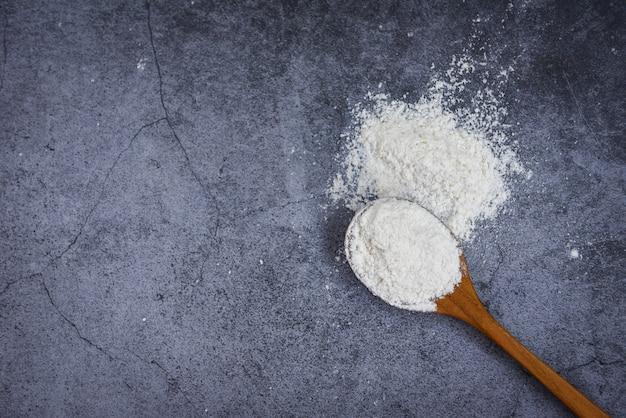 Farinha de pastelaria na colher de pau no fundo cinza, vista superior - farinha caseira para cozinhar ingredientes na mesa da cozinha