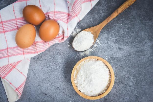 Farinha de pastelaria na tigela de madeira no fundo cinza, vista superior - ovos de farinha caseira, cozinhar ingredientes na mesa da cozinha