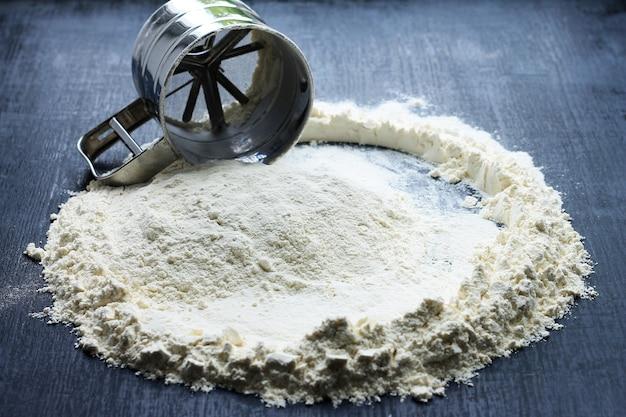 Farinha de peneira de caneca. a peneira da caneca está na farinha, farinha é dispersada ao redor no fundo escuro.