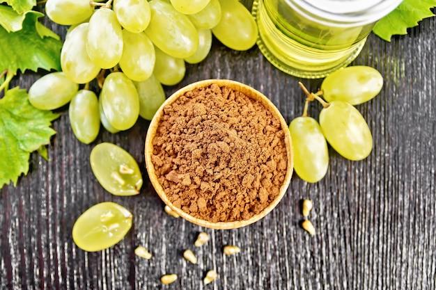 Farinha de semente de uva em uma tigela, óleo em uma jarra e uvas verdes em uma placa de madeira escura de cima
