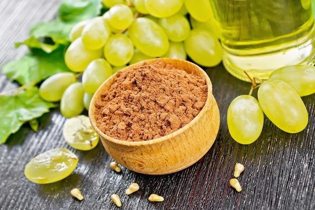 Farinha de semente de uva em uma tigela, óleo em uma jarra e uvas verdes no fundo escuro da placa de madeira