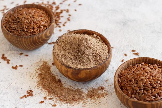 Farinha de sementes de linho crua e sementes em tigelas close-up