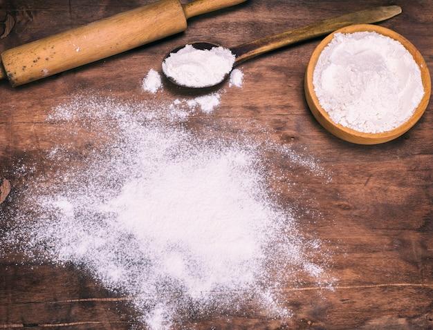 Farinha de trigo branca dispersa em um marrom de madeira