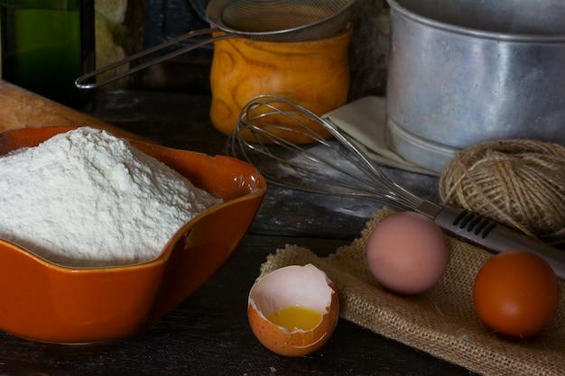 Farinha de trigo branca em cerâmica, ovo quebrado com a gema, ovos inteiros e utensílios de cozinha