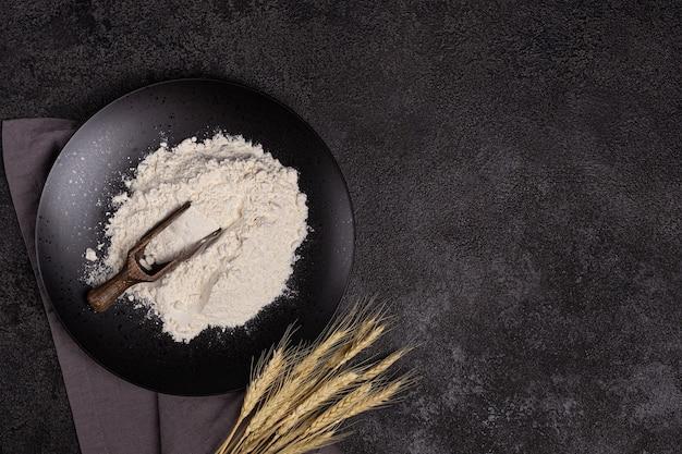 Farinha de trigo branca em uma colher de pau em um fundo escuro estrutural em um prato feito de pedra preta