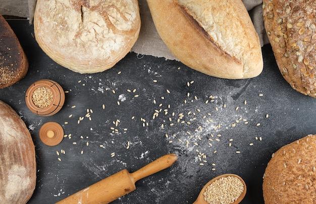 Farinha de trigo branco cozida e centeio com sementes de abóbora e girassol em uma superfície preta