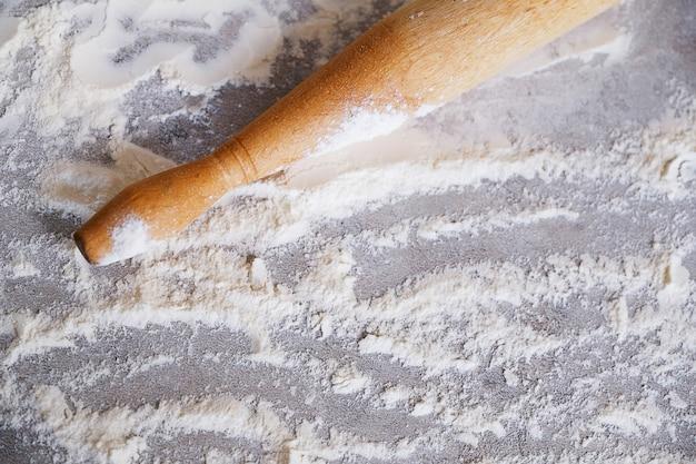 Farinha de trigo dispersa e um pino do rolo na mesa de cozinha. o processo de assar, cozinhar.