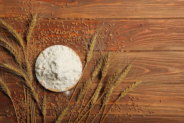 Farinha de trigo e espigas de trigo em um fundo claro