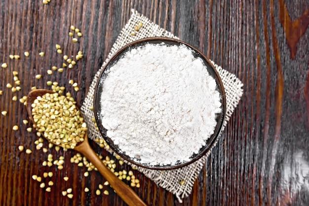 Farinha de trigo sarraceno de cereais verdes em uma tigela na sacaria, sêmolas em colheres e em uma mesa contra o fundo da placa de madeira de cima