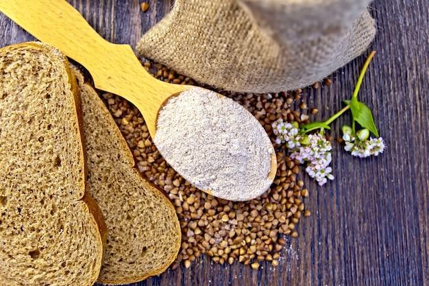 Farinha de trigo sarraceno em uma colher de pau, trigo sarraceno no saco, fatias de pão, flor de trigo sarraceno no fundo de tábuas de madeira em cima