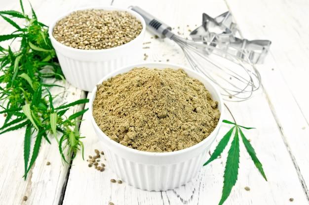 Farinha e grãos de cânhamo em tigelas, batedeira e cortador de biscoitos, folhas de cannabis no fundo de tábuas de madeira