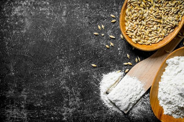 Farinha e grãos em tigelas com espátula de madeira na mesa rústica