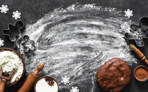 Farinha e massa com um rolo na mesa da cozinha. ingredientes para fazer um boneco de gengibre. vista do topo