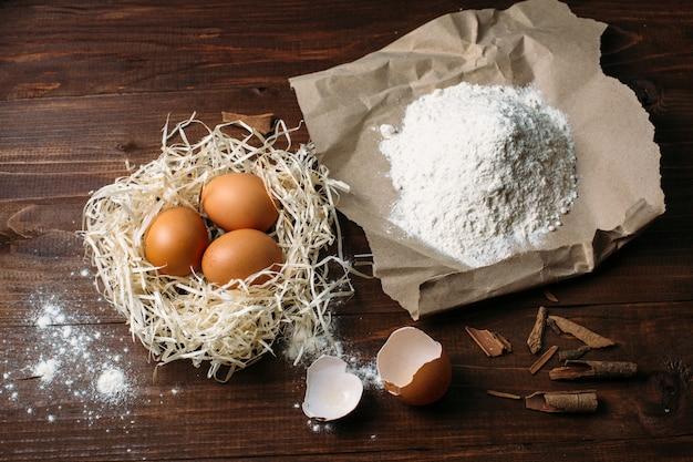 Farinha e ovos em uma placa de madeira