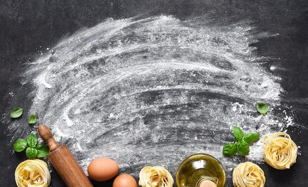 Farinha e rolo em cima da mesa. o processo de cozinhar macarrão tagliatelle na mesa da cozinha.