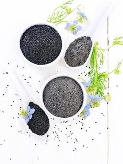 Farinha e sementes de cominho preto em tigelas, raminhos de kalingini com flores azuis e folhas verdes em um fundo de madeira clara vista de cima