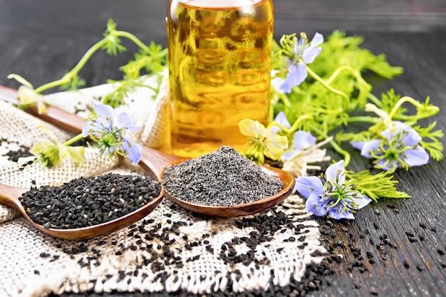 Farinha e sementes de nigella sativa em duas colheres na serapilheira, óleo na garrafa e galhos de kalingini com flores azuis e folhas verdes em um fundo de uma velha placa de madeira