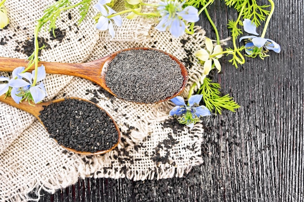 Farinha e sementes de nigella sativa em duas colheres na serapilheira, raminhos de kalingini com flores azuis e folhas verdes no fundo de uma velha placa de madeira vista de cima