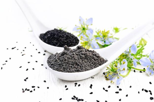 Farinha e sementes de nigella sativa em duas colheres, raminhos de kalingini com flores azuis e folhas verdes em um fundo de placa de madeira
