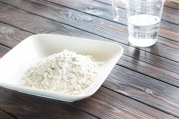 Farinha em prato branco, medindo o copo com água. raios de sol na mesa.