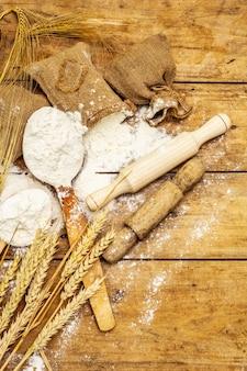 Farinha em sacos, espigas de grãos, colheres e rolos de madeira. conceito de panificação, mesa de madeira, close-up