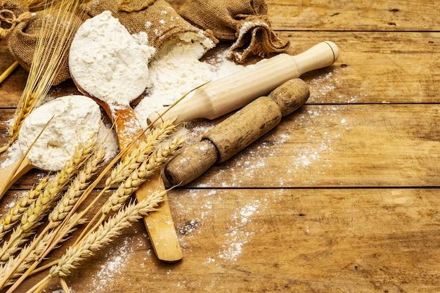 Farinha em sacos, espigas de grãos, colheres e rolos de madeira. conceito de panificação, mesa de madeira, espaço de cópia