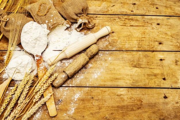 Farinha em sacos, espigas de grãos, colheres e rolos de madeira. conceito de panificação, mesa de madeira, vista superior