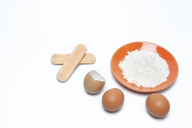 Farinha em um prato de laranja, dois ovos e uma casca de ovo no fundo branco
