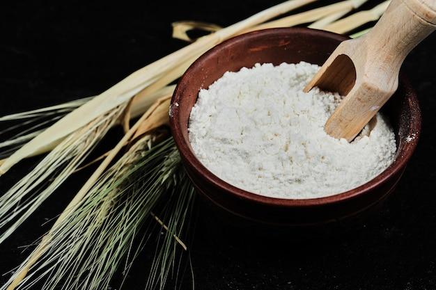 Farinha em uma tigela com trigo na mesa escura, close-up.