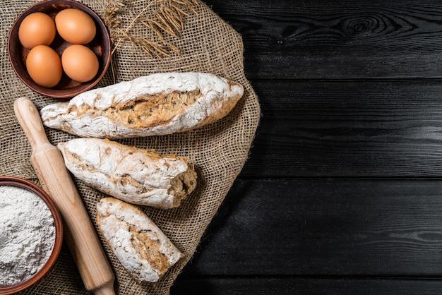 Farinha em uma tigela de madeira na mesa de madeira escura com espigas de trigo, ovos, leite e manteiga, vista superior com espaço de cópia.