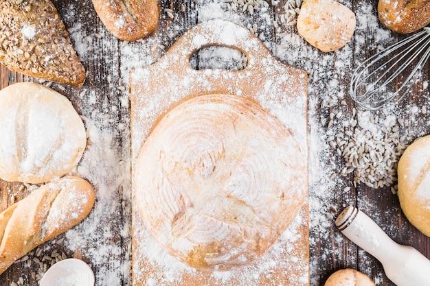 Farinha espalhada sobre o pão redondo e pães sobre a mesa