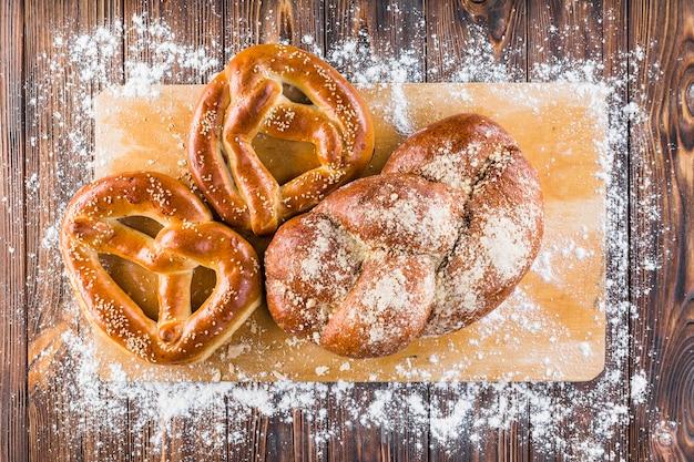 Farinha espalhada sobre o pão trançado e pretzels na tábua sobre a mesa de madeira