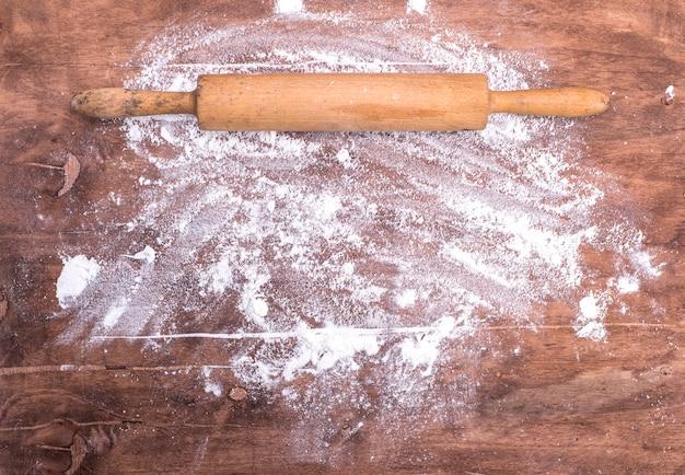 Farinha espalhada sobre uma mesa de madeira marrom