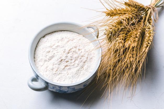 Farinha integral em tigela com espigas de trigo