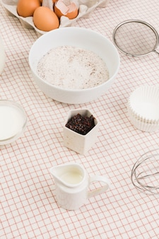 Farinha; leite; ovo; e utensílios de cozimento dispostos na mesa