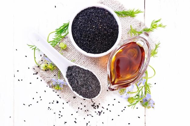 Farinha nigella sativa em uma colher, sementes de cominho preto em uma tigela e óleo em molheira na serapilheira, raminhos de kalingi com flores azuis e folhas verdes no fundo de uma placa de madeira de cima
