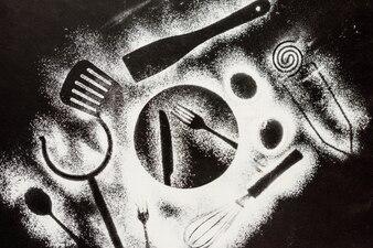 Farinha no fundo preto com formas de elementos de cozinha