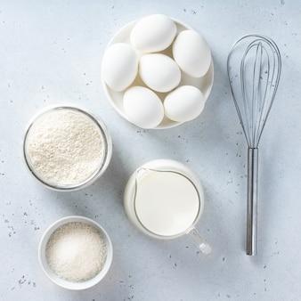 Farinha, ovo, leite, açúcar em uma mesa, vista de cima