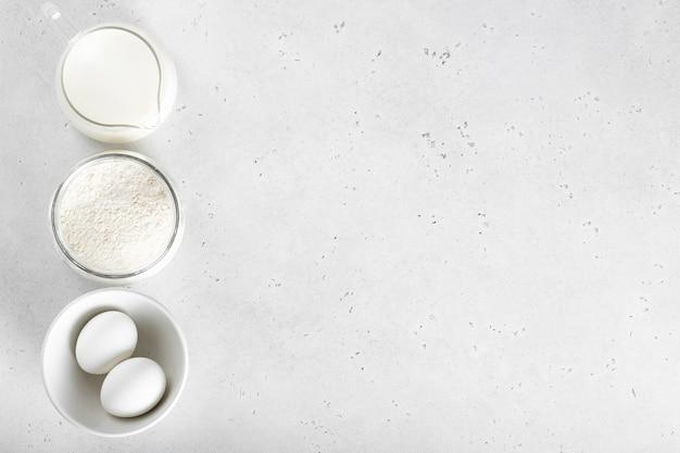 Farinha, ovo, leite em uma mesa branca, vista de cima
