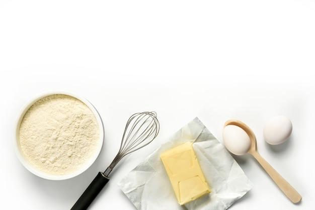 Farinha, ovos, manteiga, bata, colher, isolado no fundo branco. ingredientes para cozimento caseiro em um prato branco com espaço de cópia.
