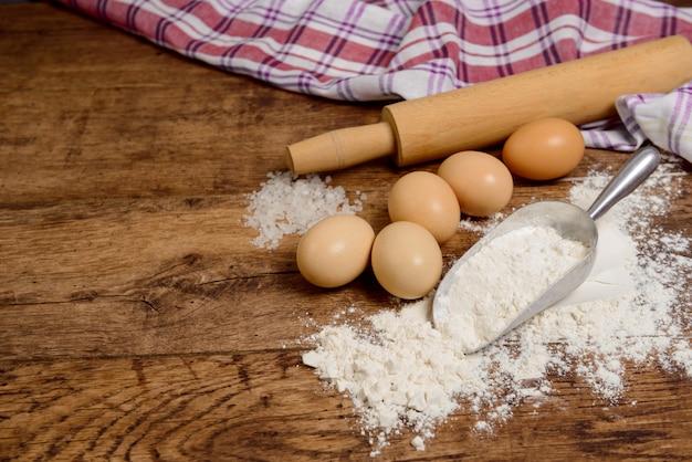 Farinha, ovos, sal, toalha, rolo na mesa de madeira pronta para cozinhar